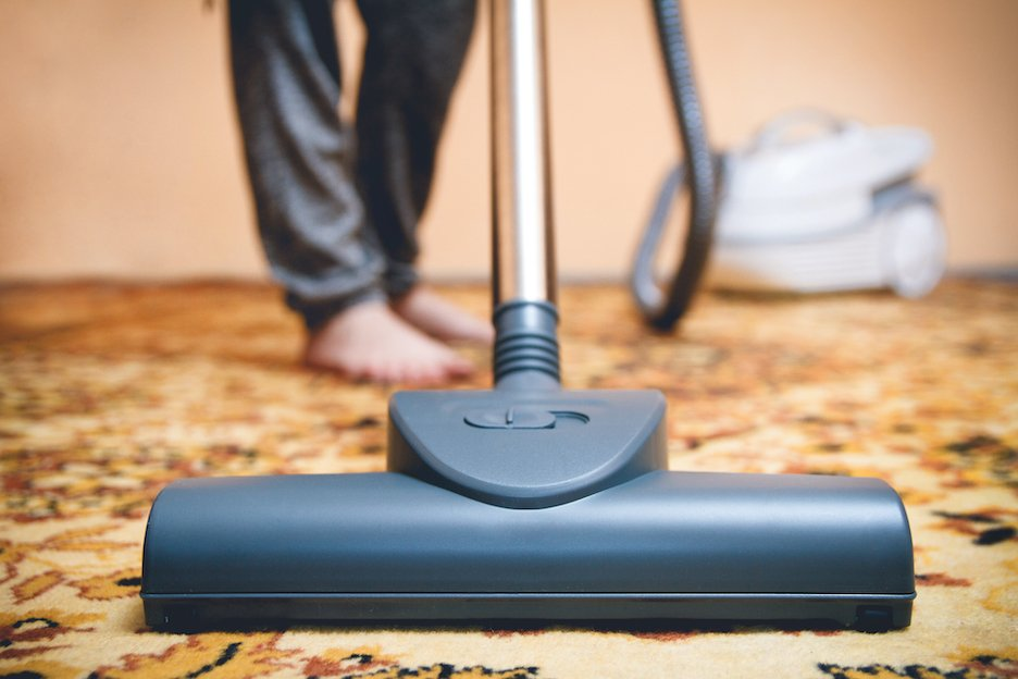 a person vacuuming the carpet