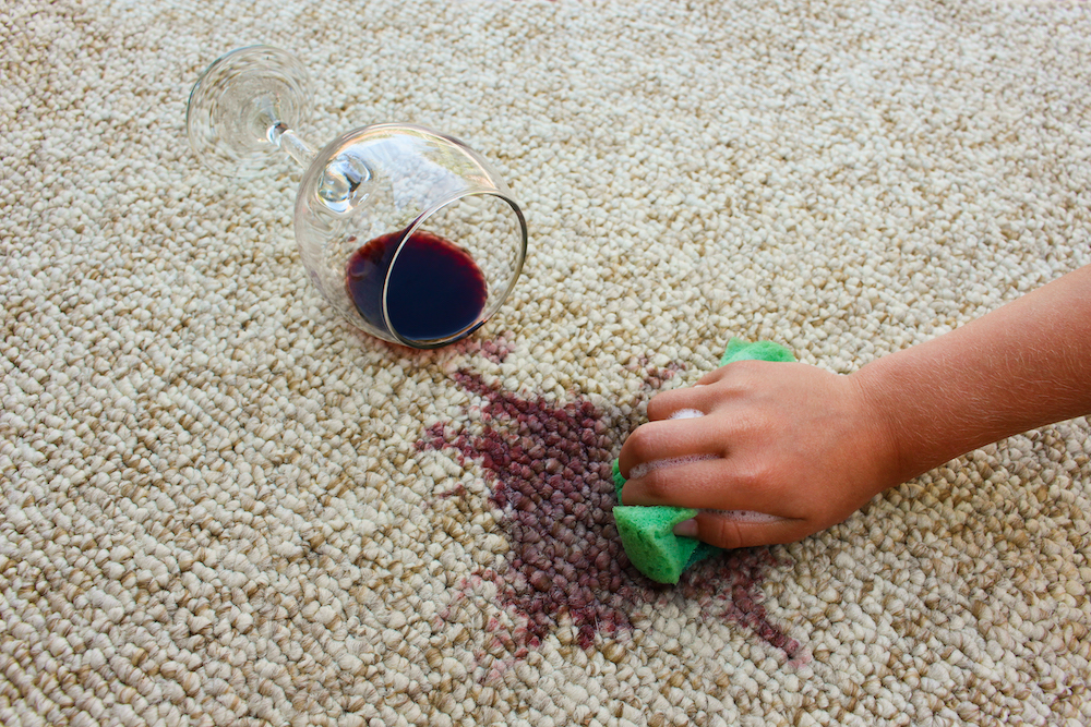 Man scrubbing red wine stain on a carpet