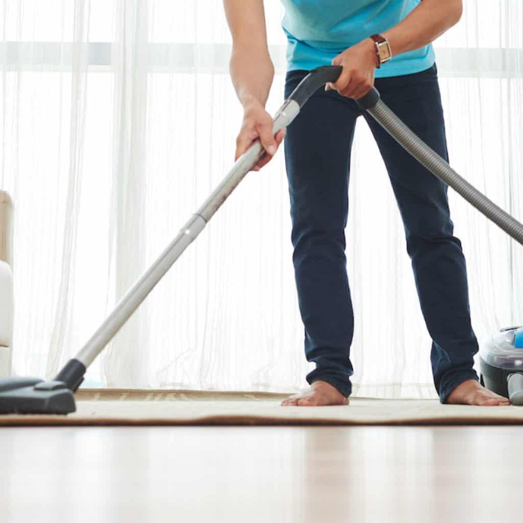 man vacuuming carpet