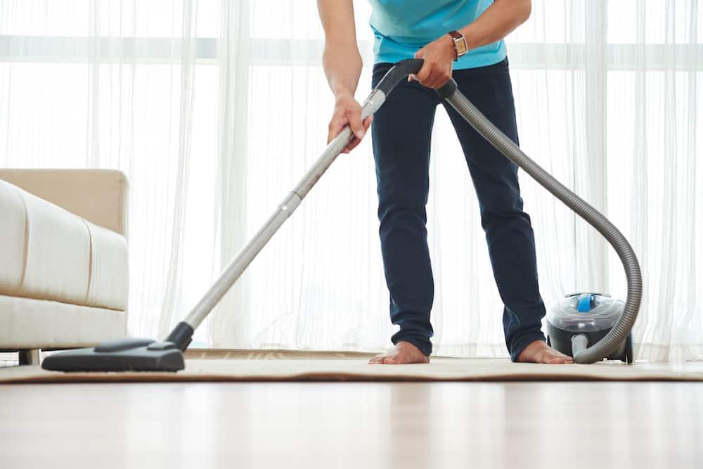 man vacuuming carpet in living room