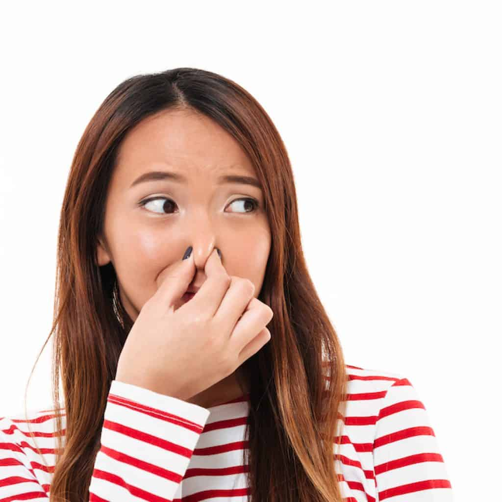 Woman pinching her nose, due to unpleasant smell