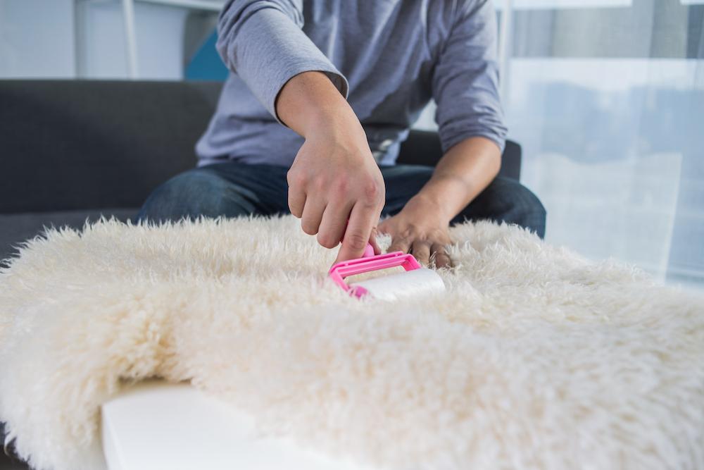 Man using lint roller on carpet